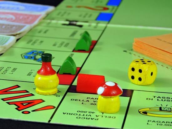 Corner of a monopoly board with playing pieces and dice