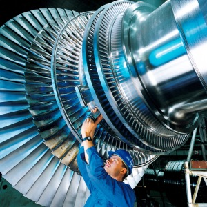 A worker installing a turbine blade on a steam turbine rotor being assembled in a Siemens factory in Germany by Siemens Pressebild