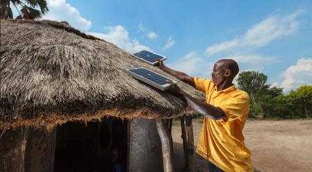 A customer installing a ReadyPay Solar Home System (SHS) -Photo by Fenix International